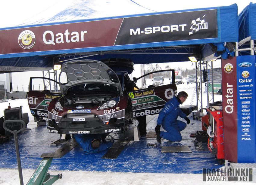 Juho Hännisen Ford Fiesta WRC:tä huollettiin aika-ajon jälkeen. Mekaanikot saivat tehdä töitä käytännössä sään armoilla. Huomioitavaa tuossa vaiheessa oli myös se, miten Hännisen Fordissa ilmanottoaukko etupuskurin alaosassa oli pienellä luukulla, kun muissa Fordeissa avoin osa oli paljon suurempi.